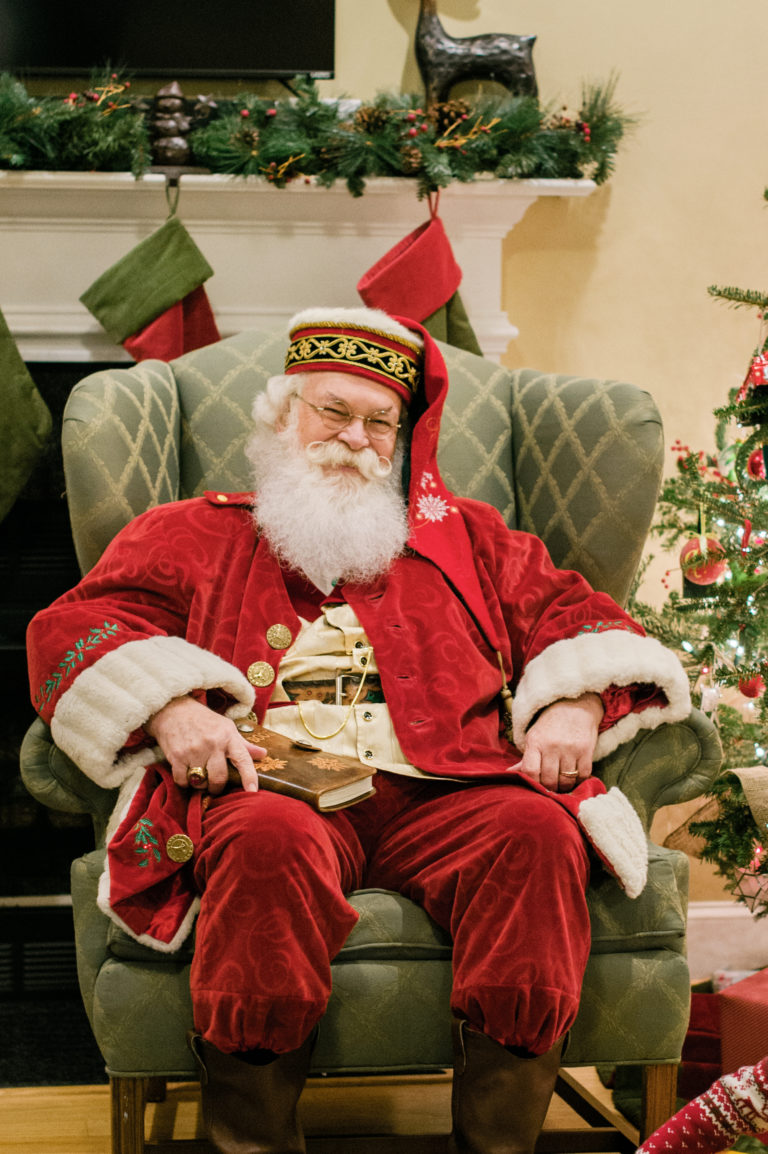 A man dressed as Santa Claus sits in an easy chair in front of a fireplace of stockings.