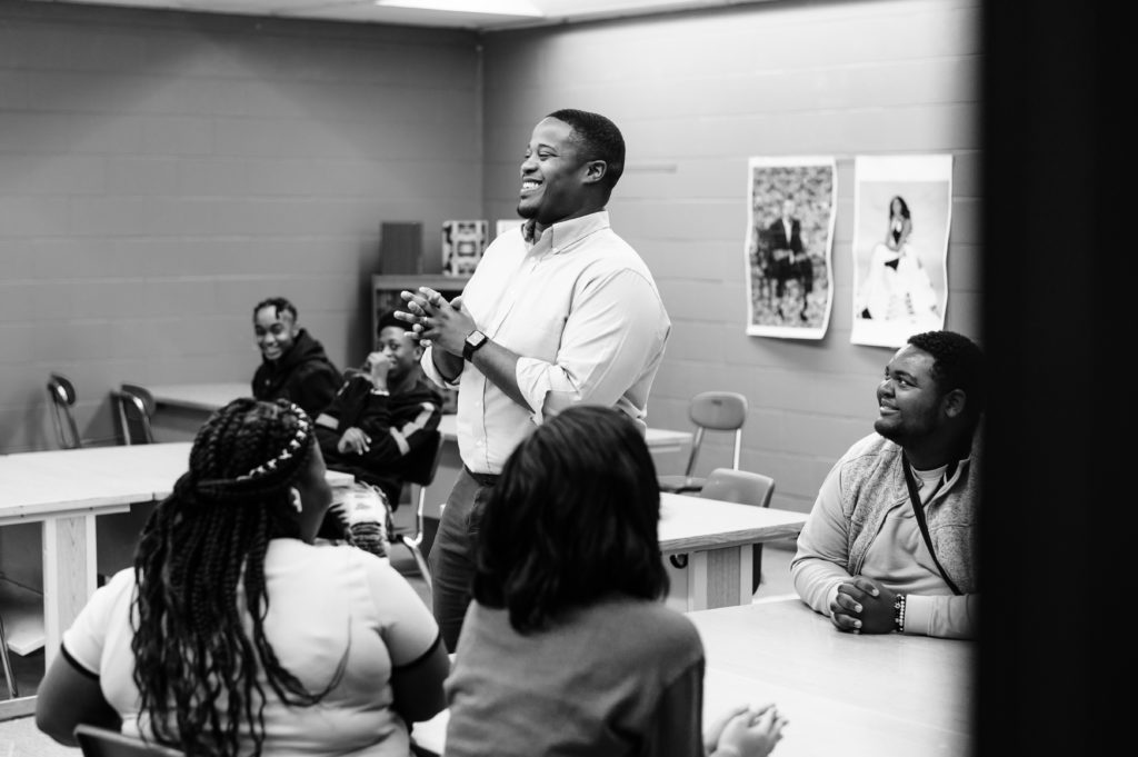 Cyril Jefferson stands in the middle of a classroom smiling, surrounded by students.