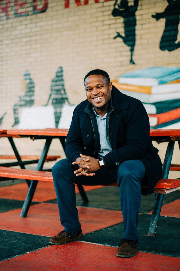 Cyril Jefferson sits on a bench at a picnic table and smiles at the camera.