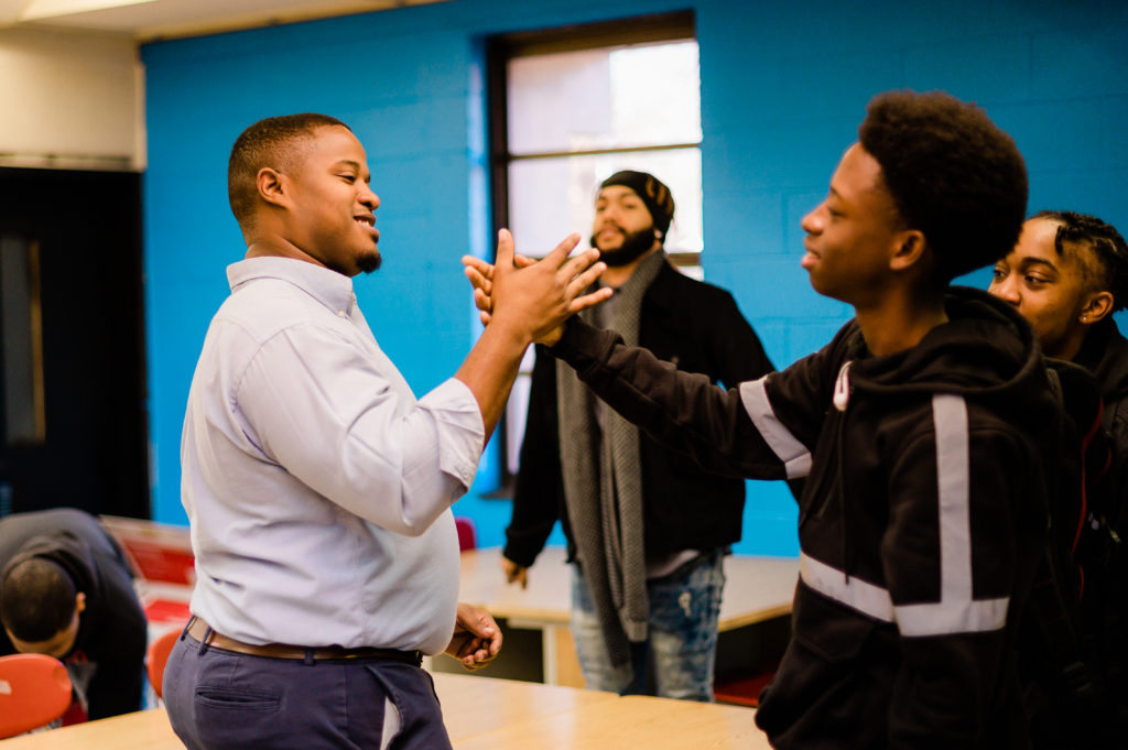 Cyril Jefferson and a student perform a handshake in a classroom.