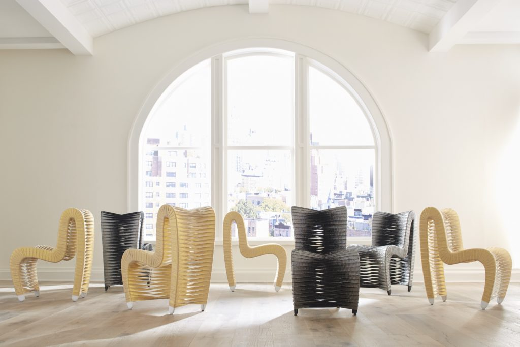 A showroom floor with 6 modern chairs sitting in front of an arched glass window.