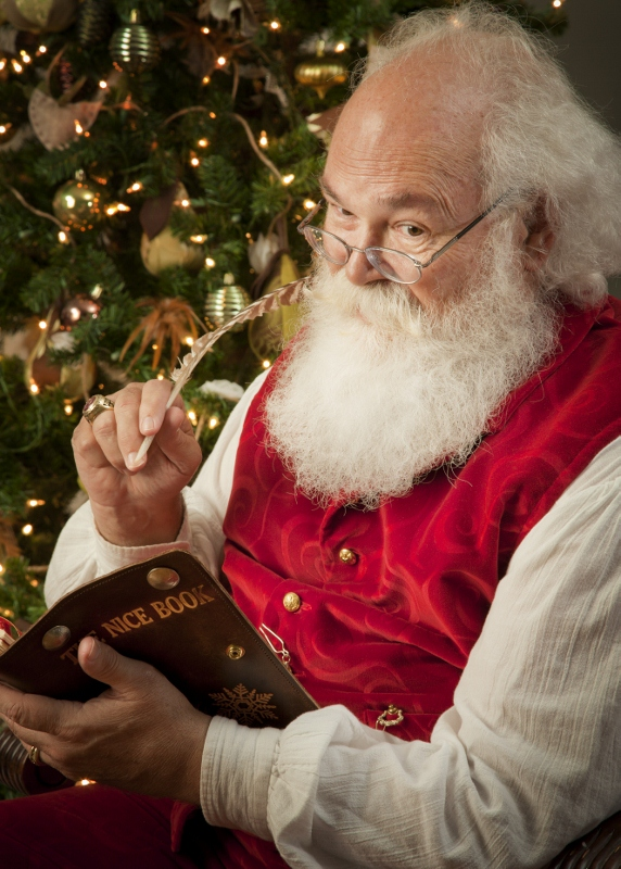 Santa Cliff, a man dressed as Santa Claus, sits in front of a tree looking in a book.