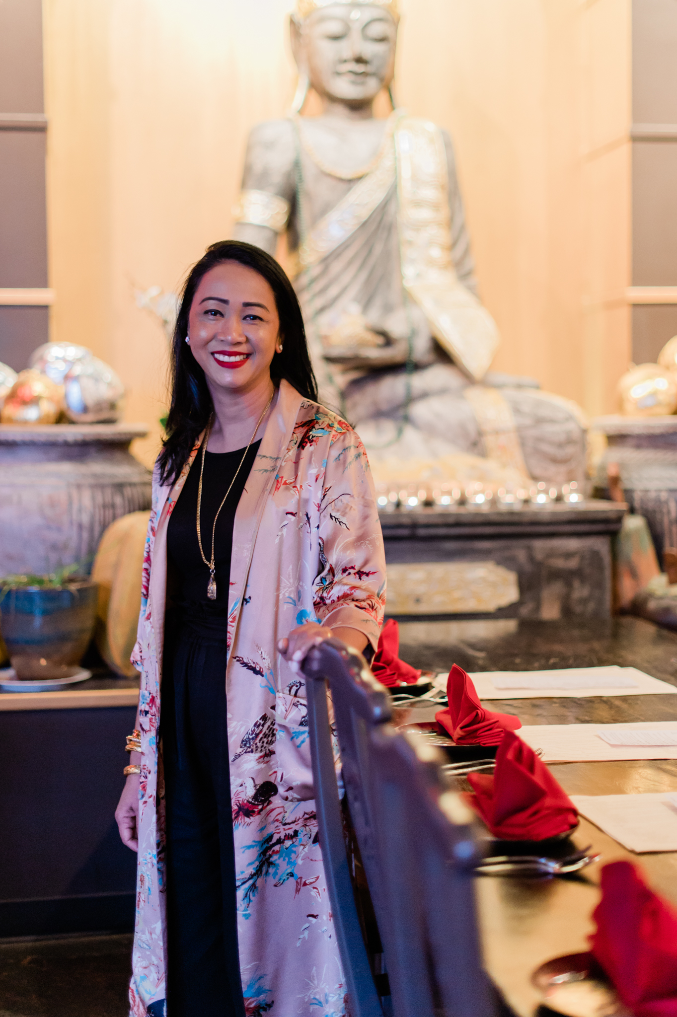 Tu Sen, owner of 98 Asian Bistro, wears a silk kimono over a black dress, and stands in the restaurant in front of a Buddha statue.