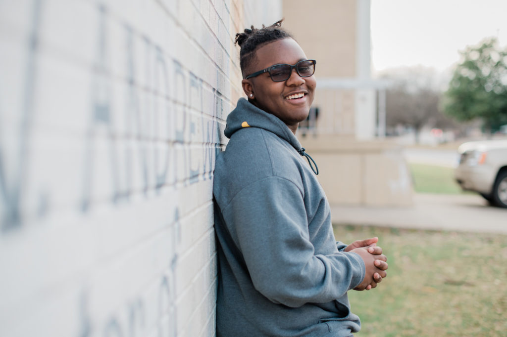 Isaiah Tatum, a student in High Point at T. W. Andrews High School leans on a wall, smiling.