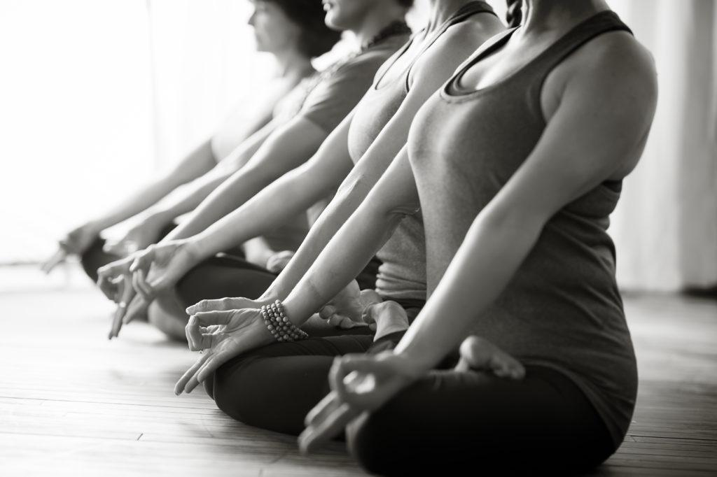 A row of women sit cross legged, meditating at Pure Light Yoga.