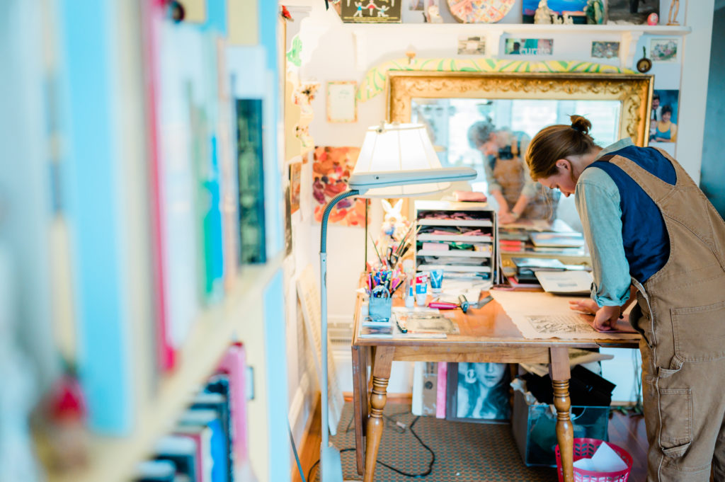 Annabella Boatwright leans over her artist's workbench working.