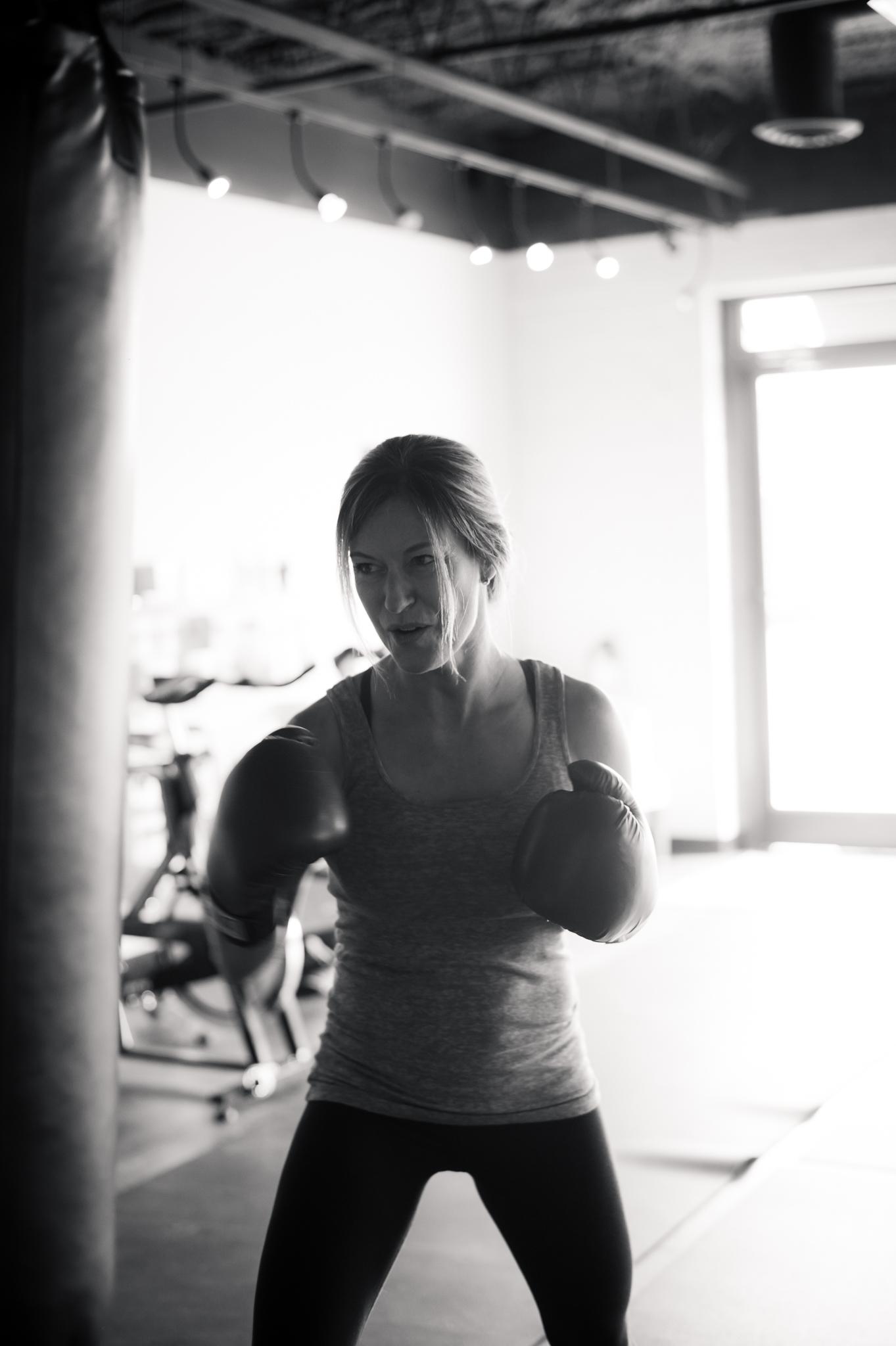 Lori Teppara wears boxing gloves and boxes a punching bag at FIT HUB.