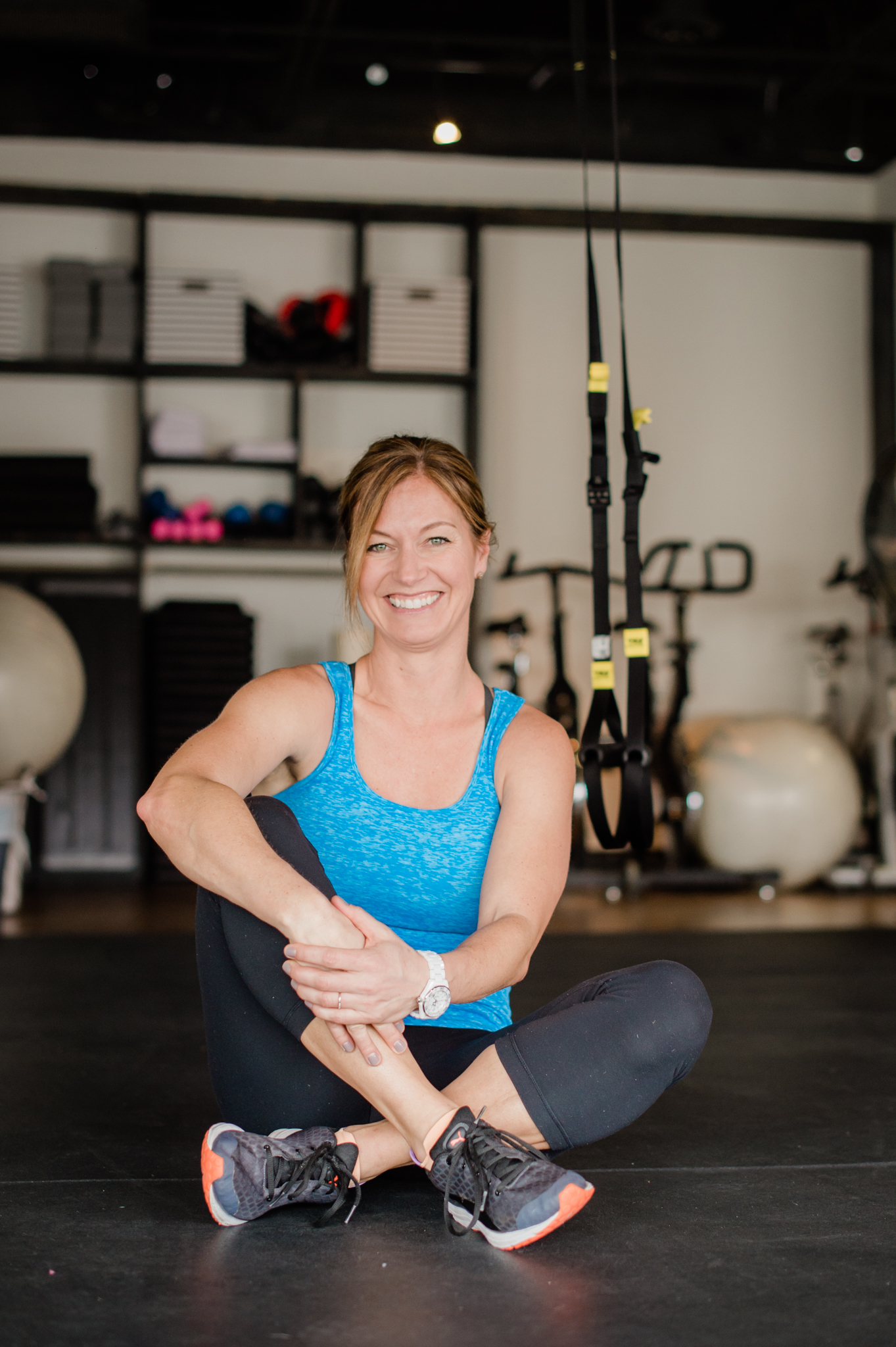 Lori Teppara sits on the floor of FIT HUB smiling.