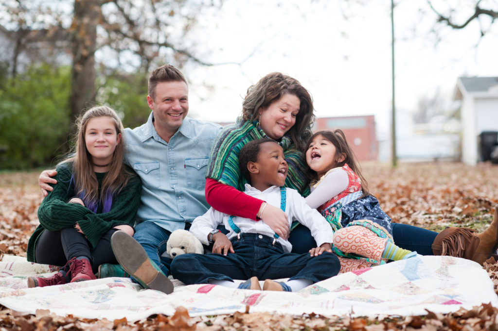 Shane Key sits on a blanket in leaves with his wife, his two daughters, and his son.