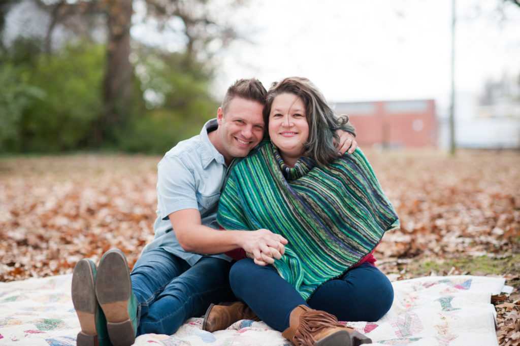 Shane Key and his wife sit on a blanket in the leaves.