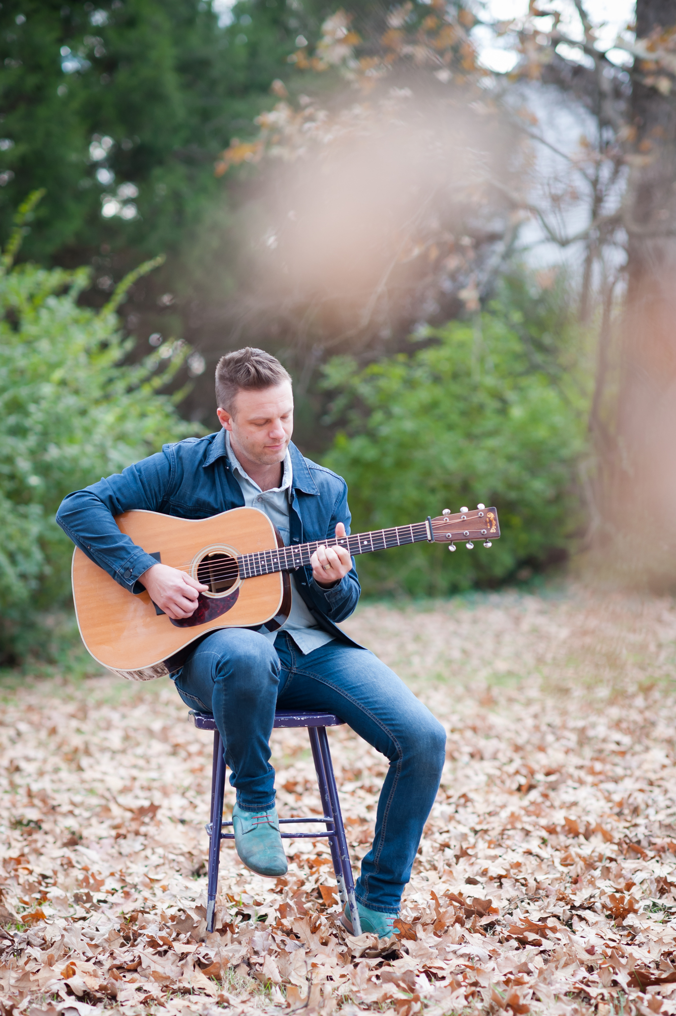 Shane Key sits on a stool in the leaves playing the guitar.
