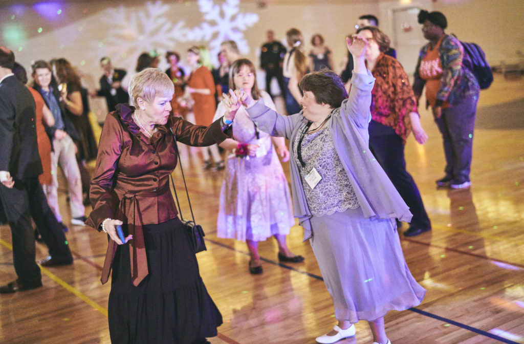 Two women dance together in the gym, while other prom guests watch.