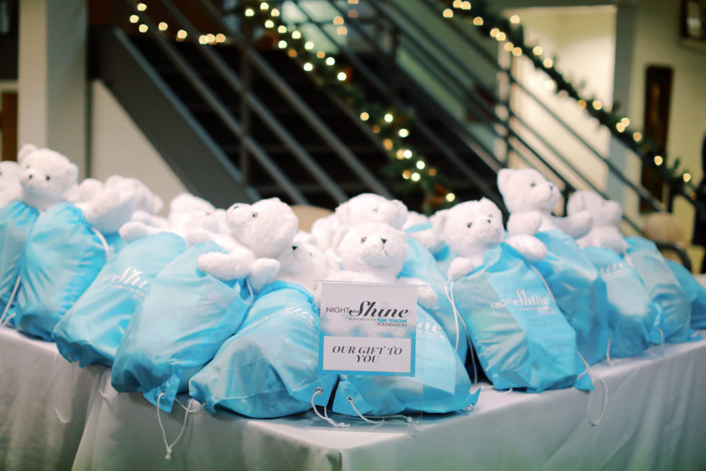 """White teddy bears are in blue bags laying on a table with """"Night to Shine"""" cards on it."""