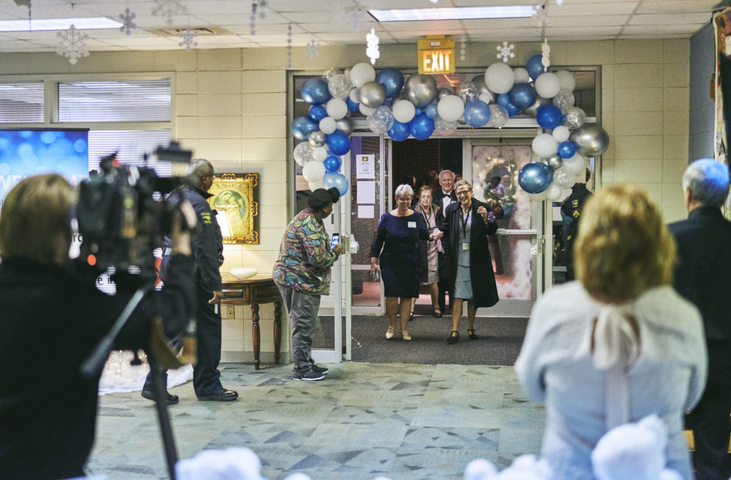 Two women walk under a blue and silver balloon arch into a church as people on the sidelines clap and smile.