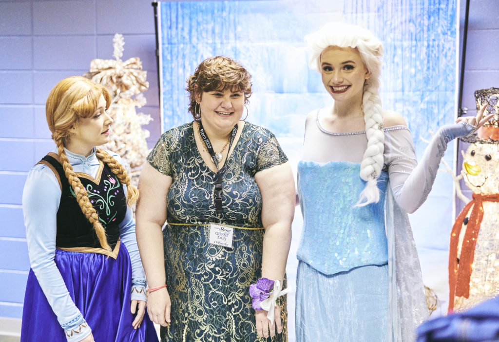 A girl in a dress stands between two actresses dressed as Princess Elsa and Princess Ana from Disney's Frozen.