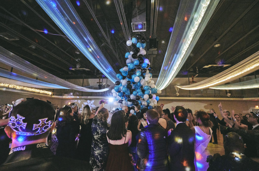 A dance floor with bright lights and a balloon sculpture of black and blue and white balloons. Groups of party goers dance under the balloons.