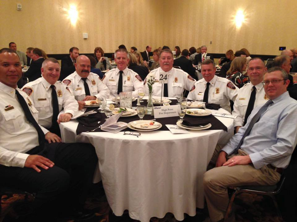 High Point Fire Chief Tommy Reid sits at a banquet table with other fire department staff. He is awarded the 2015 Volunteer of the Year at a Chamber event in February 2016.