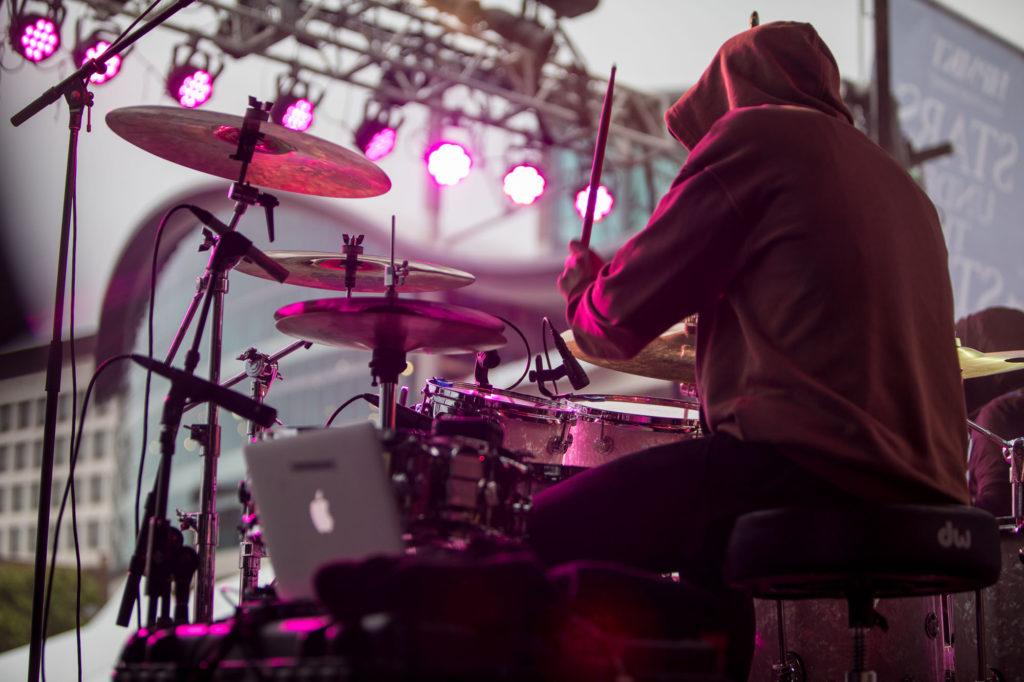 A drummer wearing a hoodie plays drums under pink concert lights.