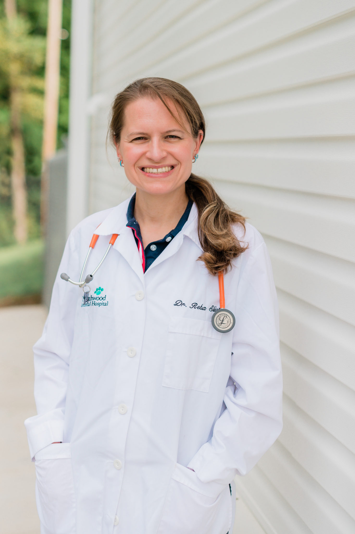 Dr. Silvka stands smiling at the camera, wearing a Northwood Animal Hospital coat.
