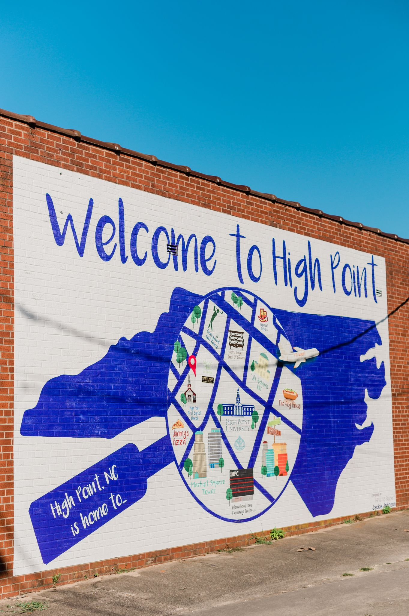 """A mural that says """"Welcome to High Point."""" A purple shape of North Carolina has a circle painted over it with specific locations to High Point."""