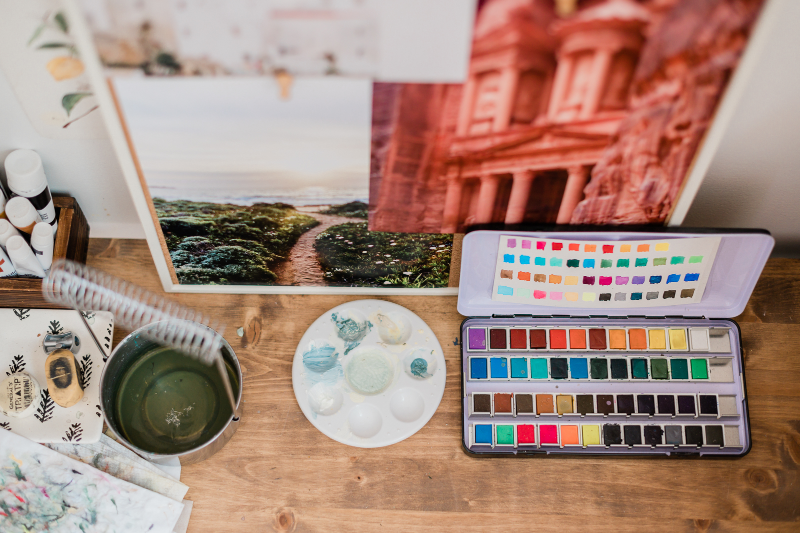 A desk has a palette of paints on it, with artwork in the background.