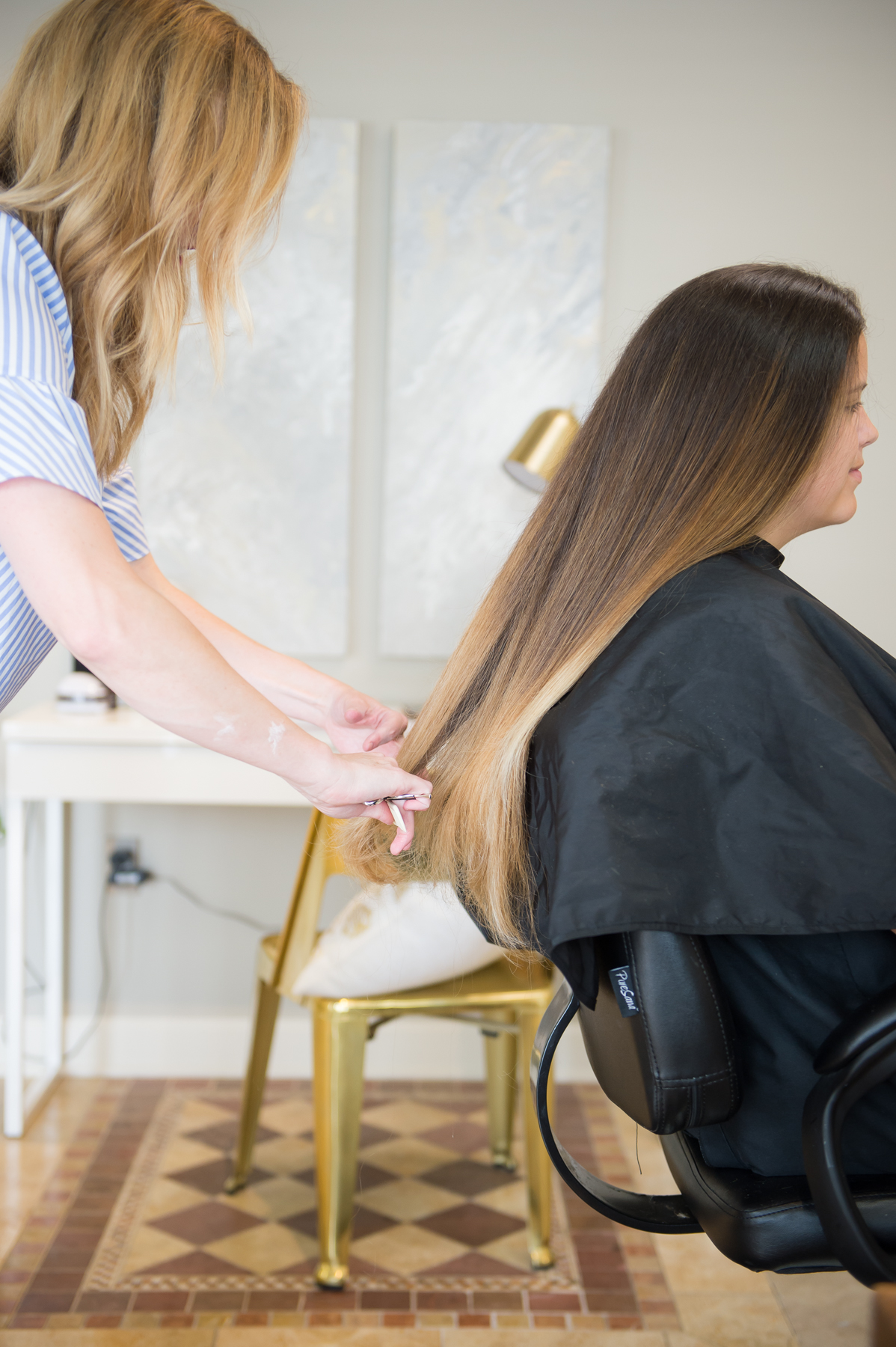 Brittany Hall straightens out the hair of a woman sitting in a salon chair.