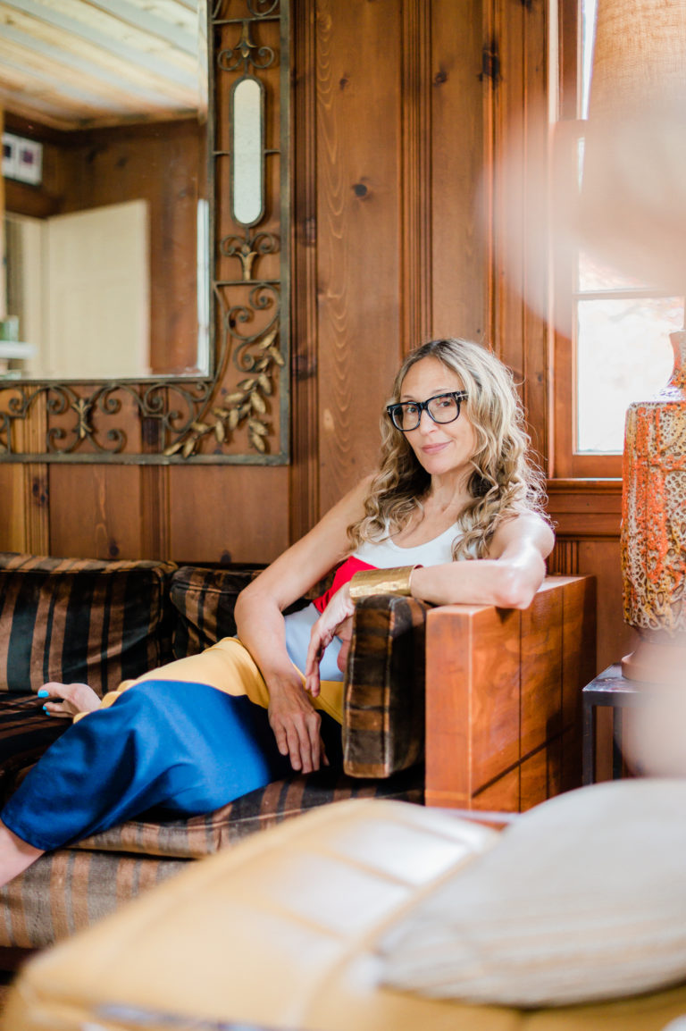 A woman in big glasses and a bright dress lounges on a wooden, cushioned sofa..