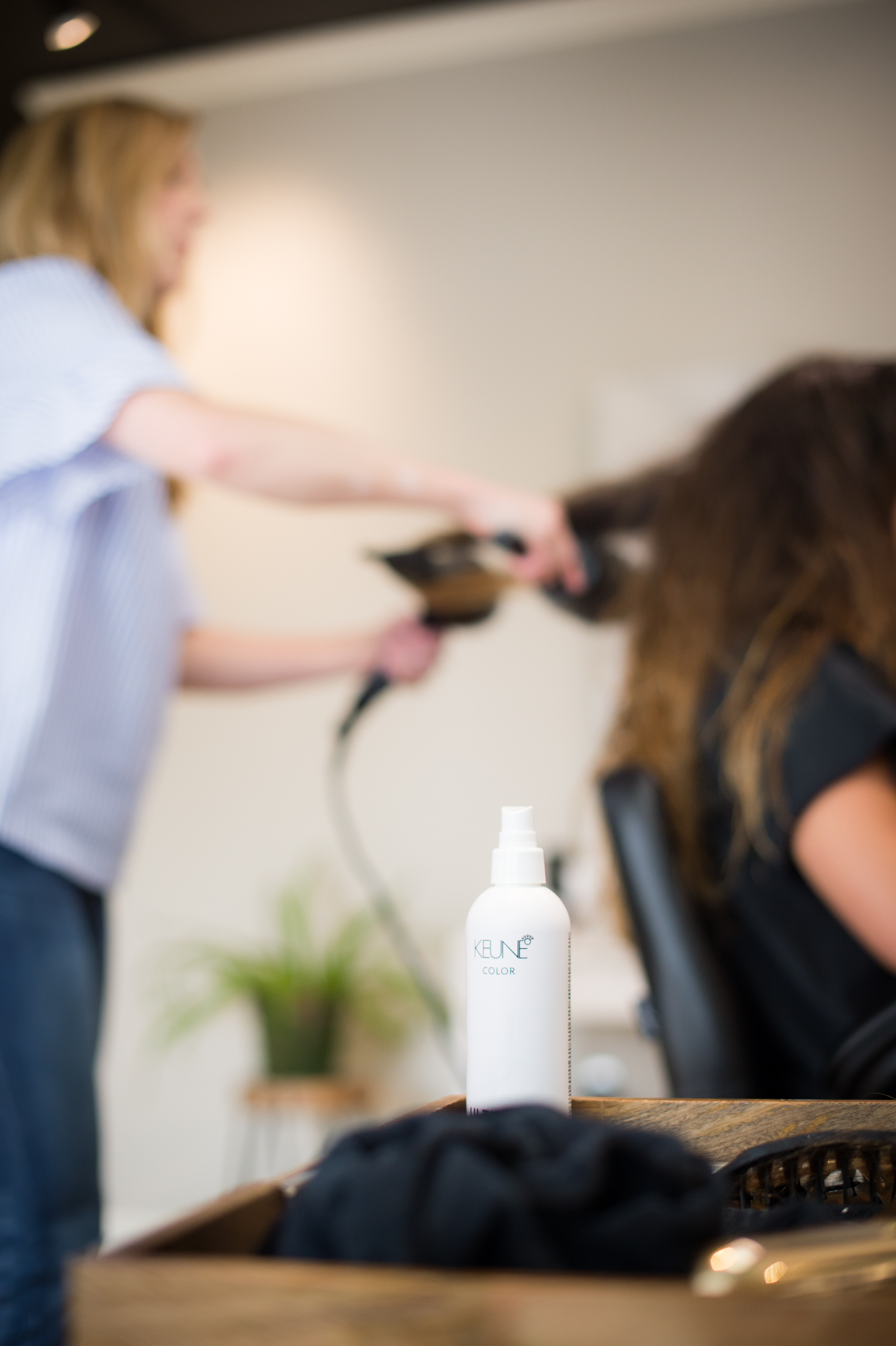 Brittany Hall blow dries a woman's hair out of focus with a bottle of hair styling product in the foreground.