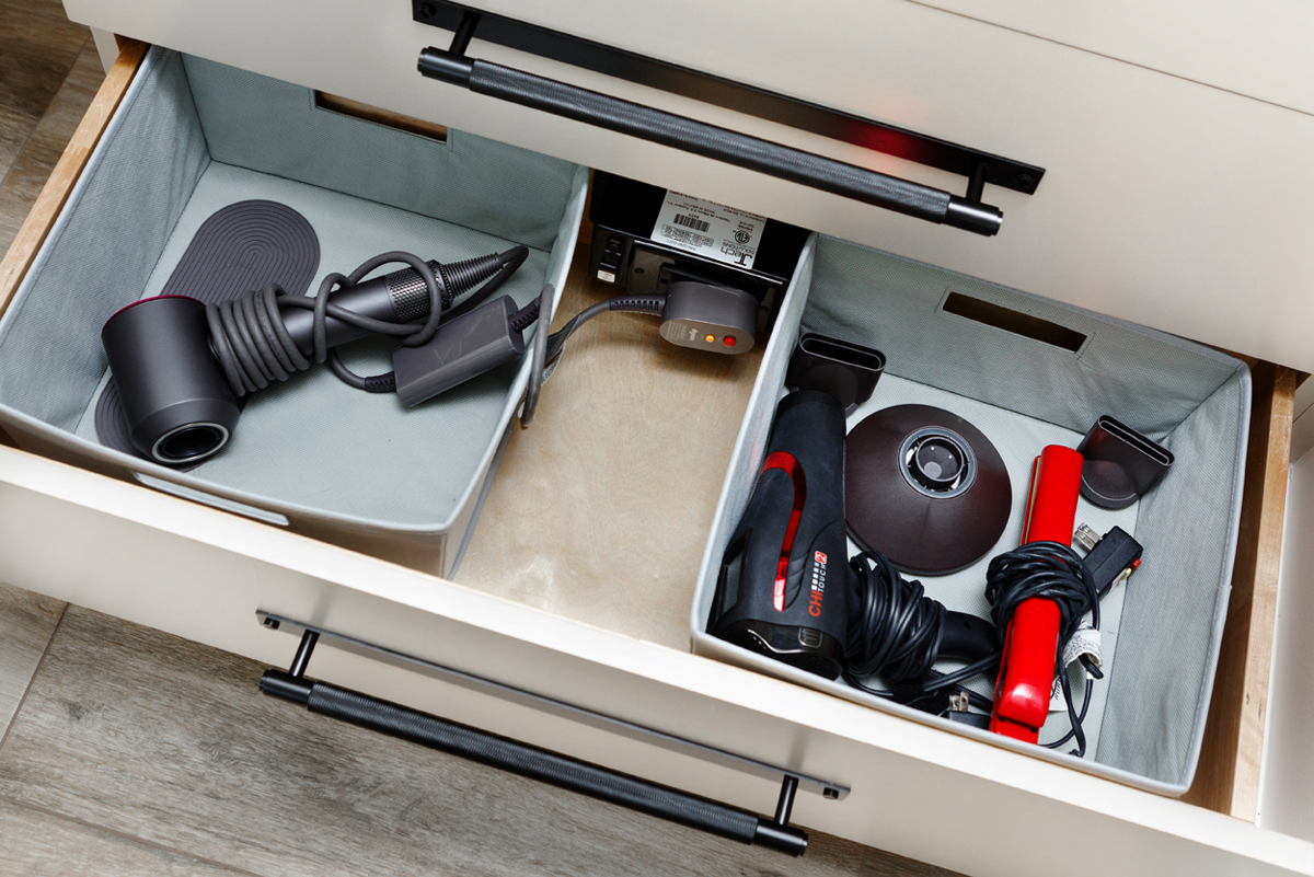 An open counter drawer with a blow dryer and several other hair tools.