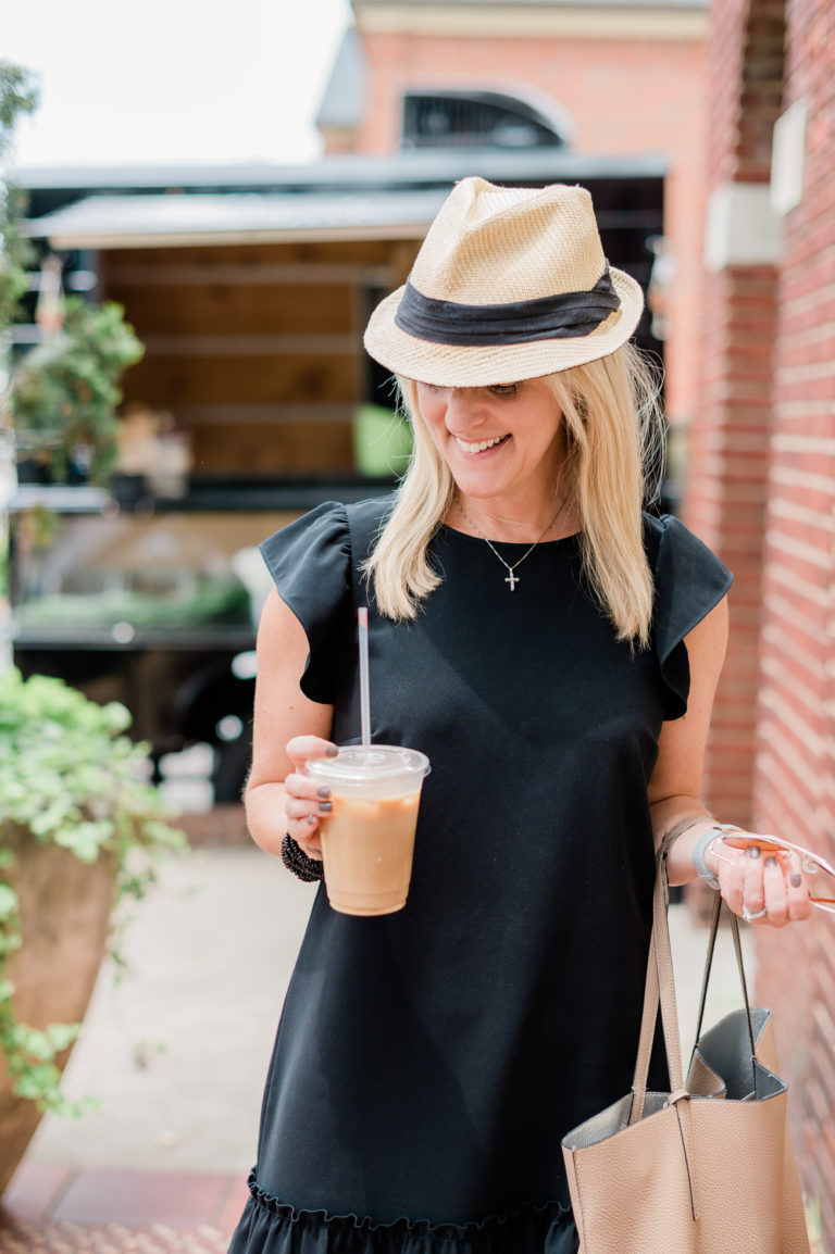 A woman in a black dress wearing a straw and black hat smiling and holding an iced coffee.