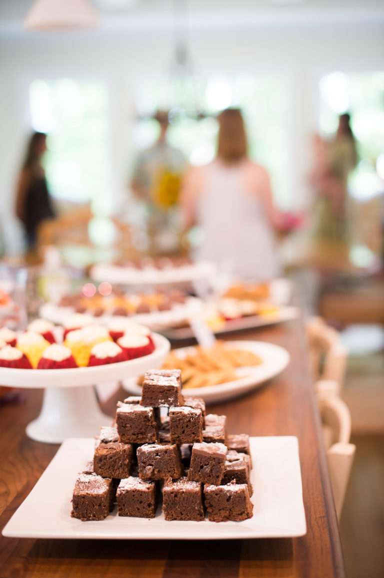 Plate of brownies sits on a table with people in the background.