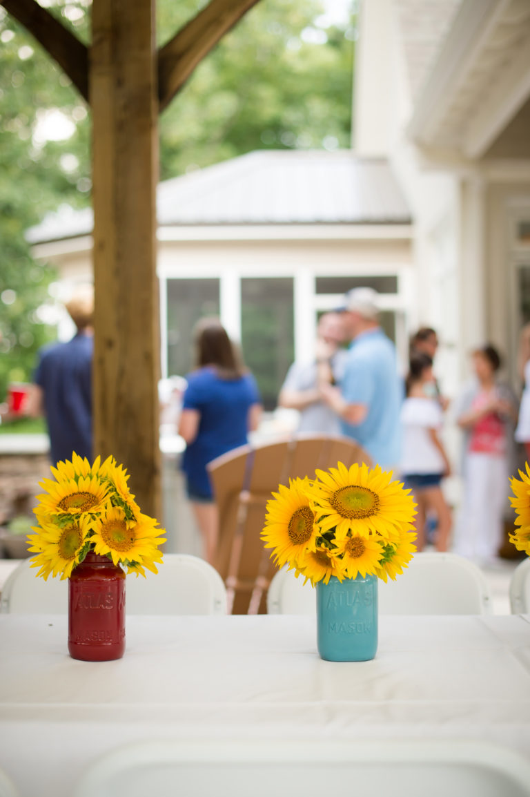 Vases of sunflowers sit on a table with people in the background.