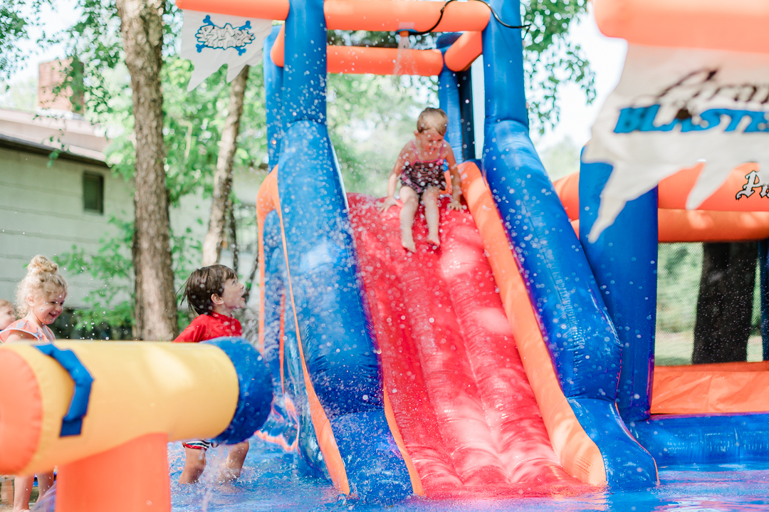Kids play on inflatable water slide outside.