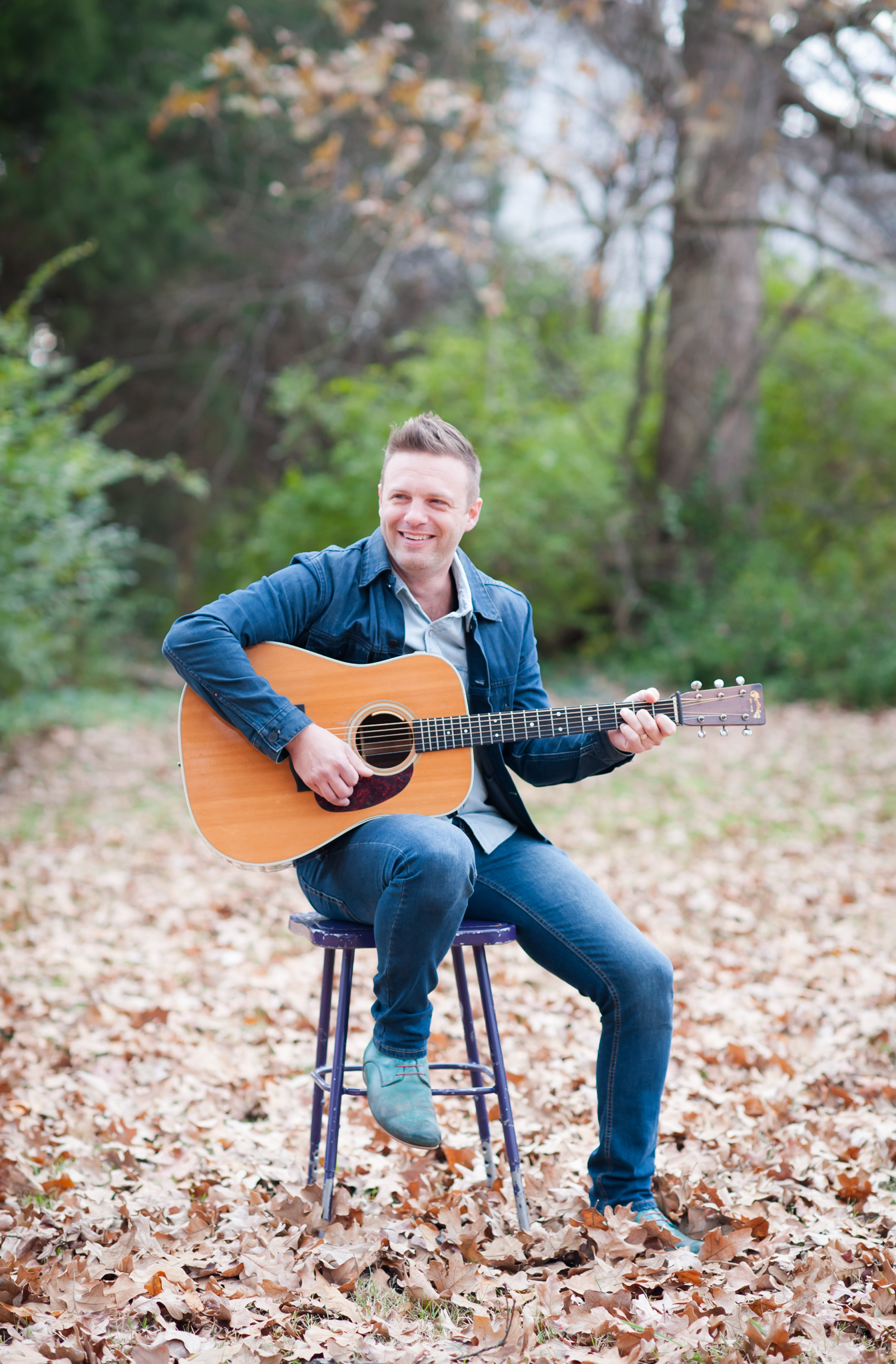 Shane Key, High Point musician sits on a stool holding a guitar.