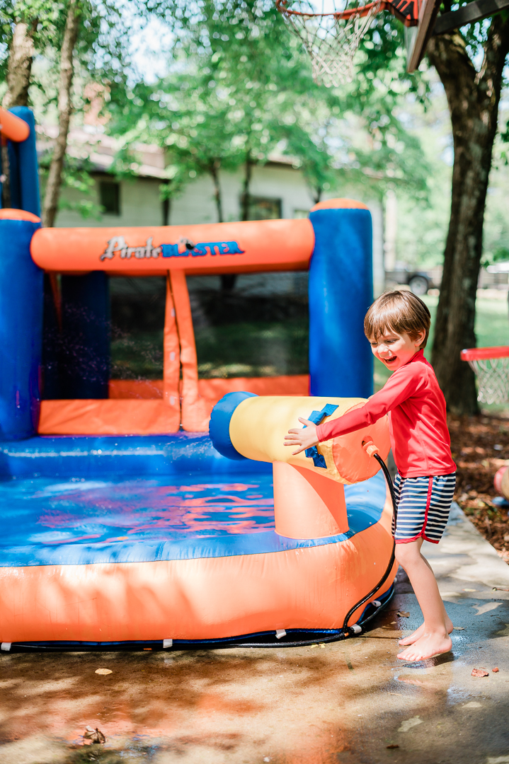 A little boy wearing a swimsuit plays with blow up water toy.