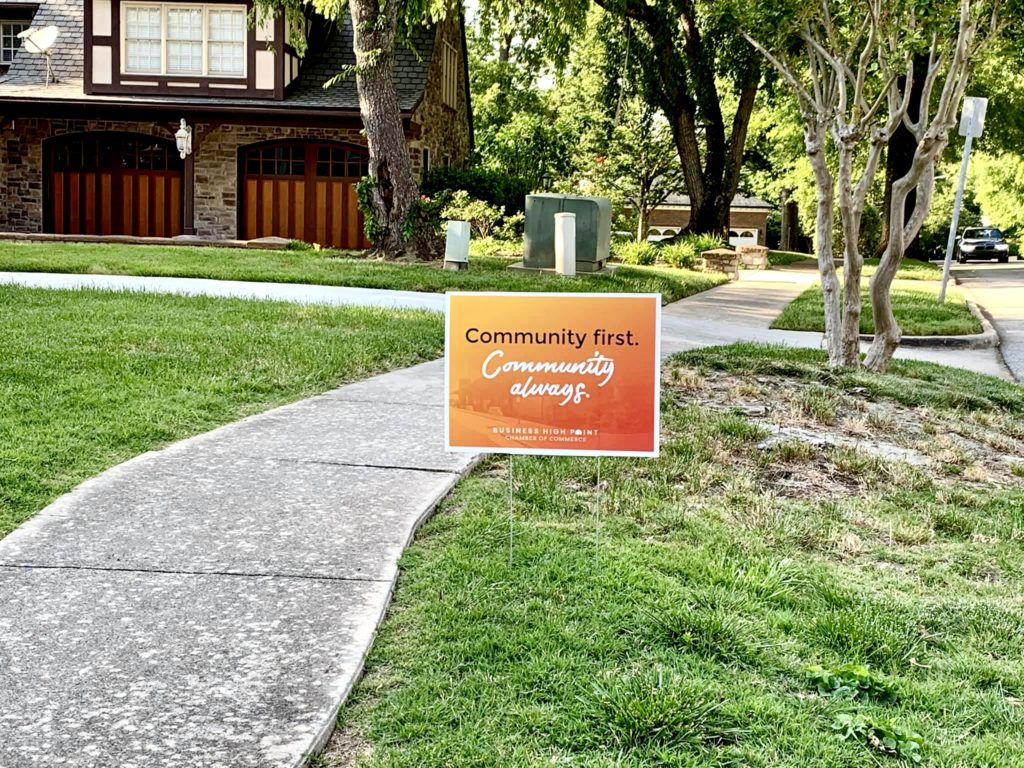 """A yard sign that says """"Community First. Community Always."""" sits in the grass."""