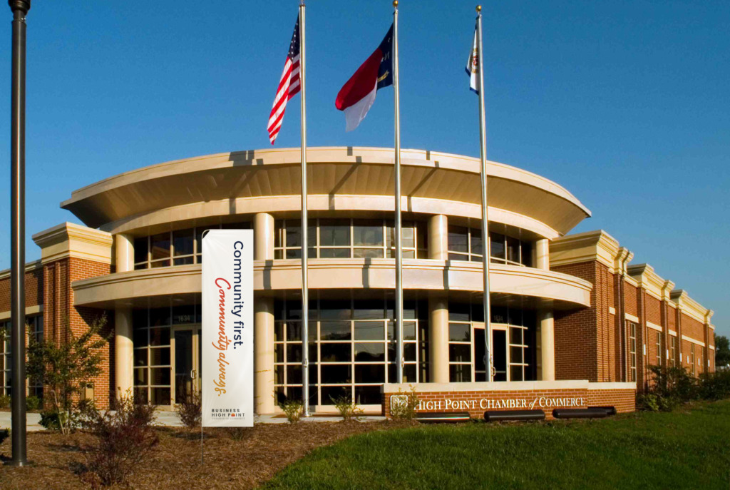 """The Business High Point Chamber of Commerce building with a flag that says, """"Community First. Community Always."""" on it."""