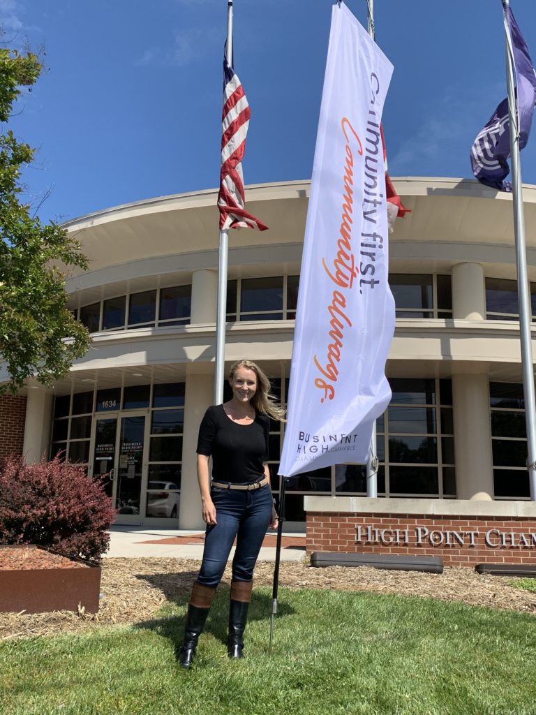 """A woman stands in front of the Business High Point building beside a """"Community First. Community Always."""" flag."""