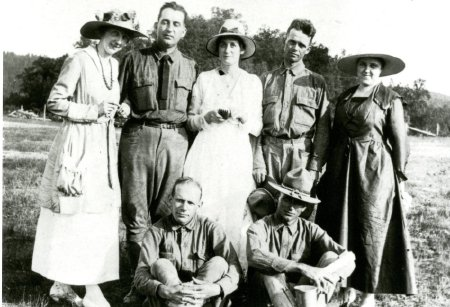 An antique photo of a group of people, the men wearing war uniforms.
