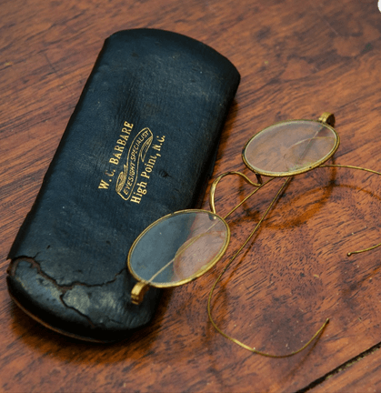 A photo of antique eyeglasses and eyeglasses case.