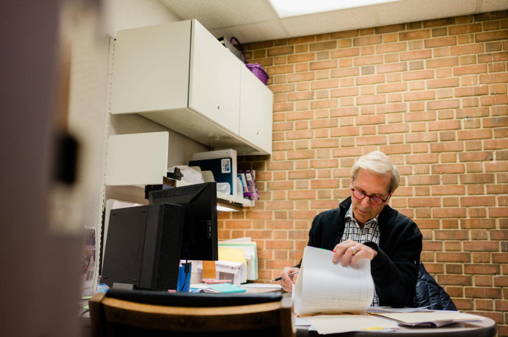 Dr. Frosty Culp, Retired High Point Dentist and volunteer at CCHP sits at his desk filling out paperwork.