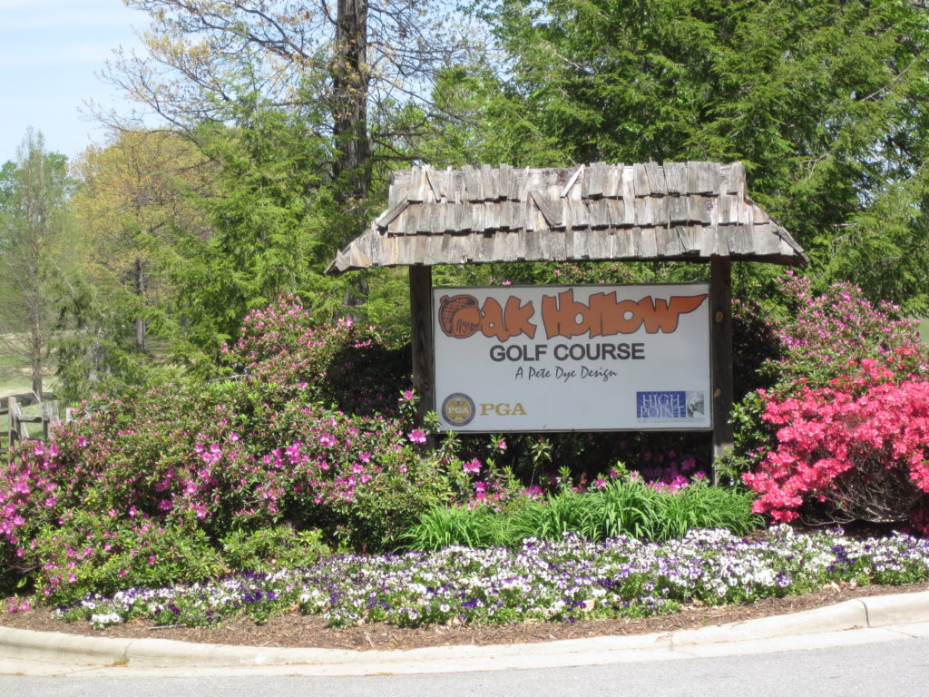 """A sign sits among flowers and shrubs that reads, """"Oak Hollow Golf Course."""""""