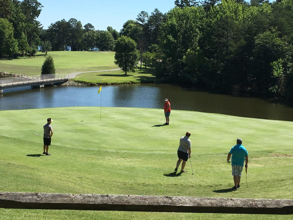 Golf players stand on Oak Hollow Golf Course.