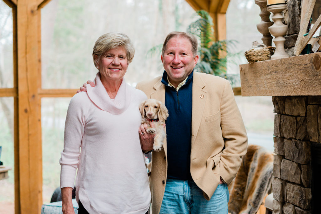 Jayne and Paul Lessard stand smiling and holding their dog.