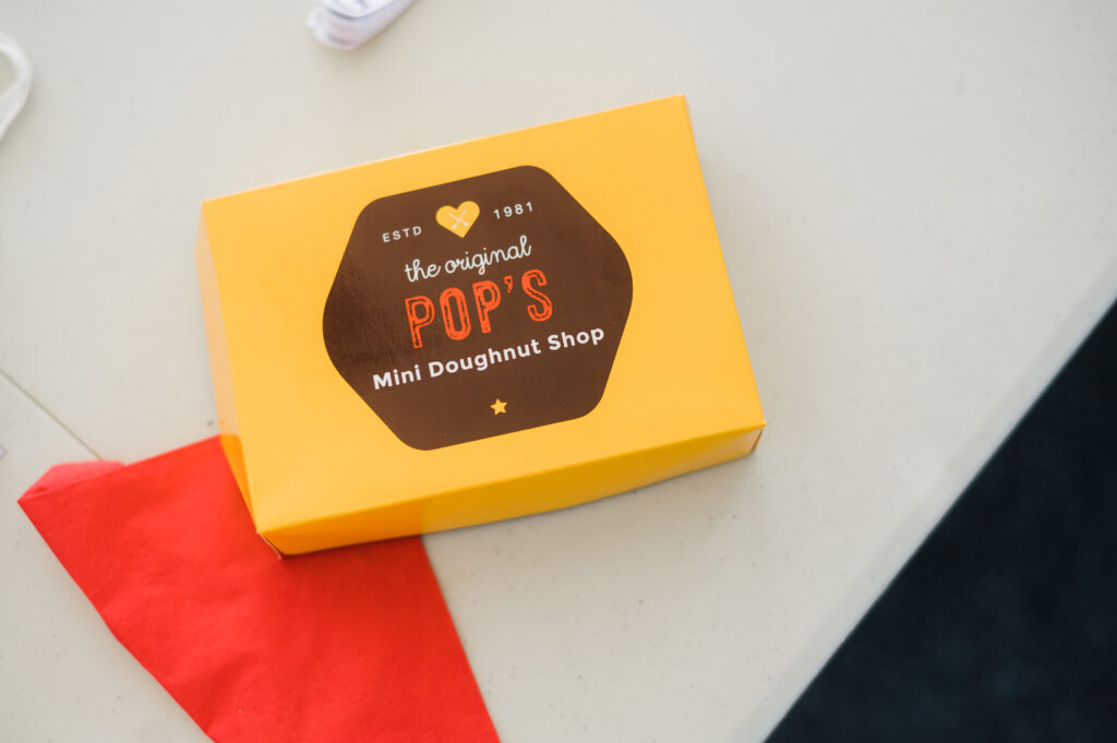 "A yellow box with a logo on it that says, ""Pop's Mini Doughnut Shop."""