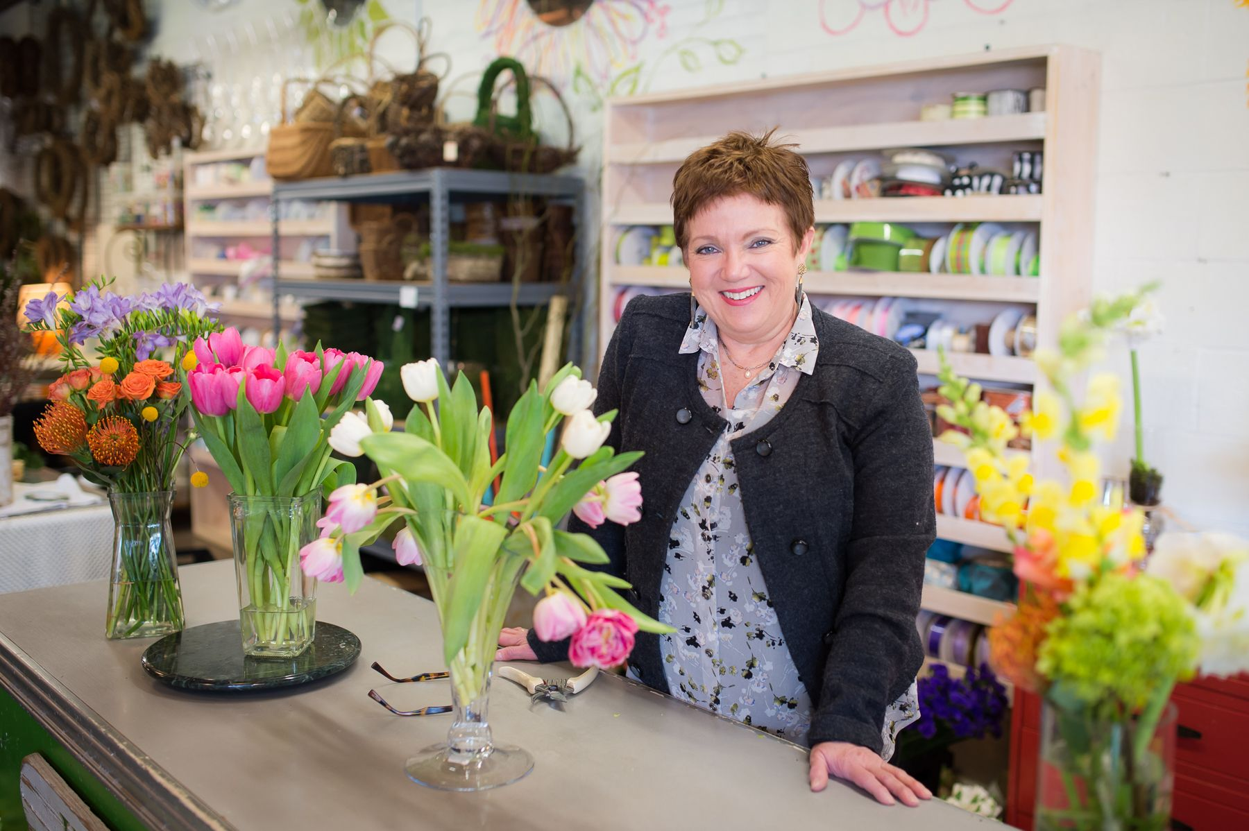Sami Price, owner of Just Priceless, stands smiling at a counter with several vases of cut flowers.