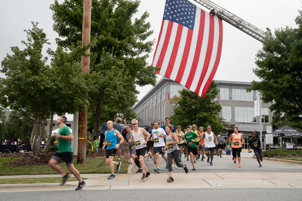 Group of runners run outside of High Point Medical Center. An American flag hangs over the runners.