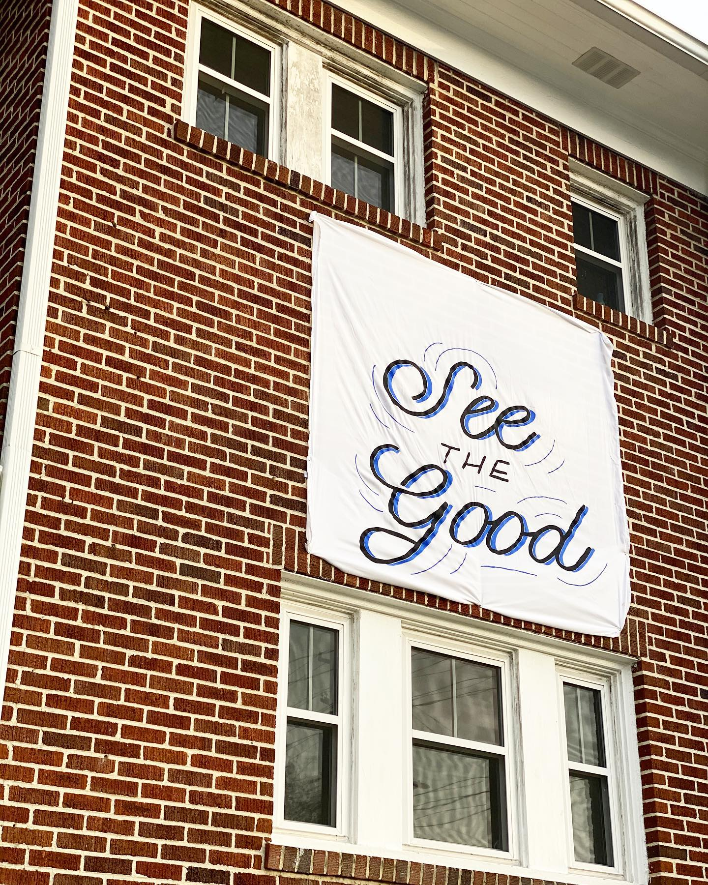"Close up of the sheet that says ""See the Good,"" hanging on The Barbour Spangle Design building."