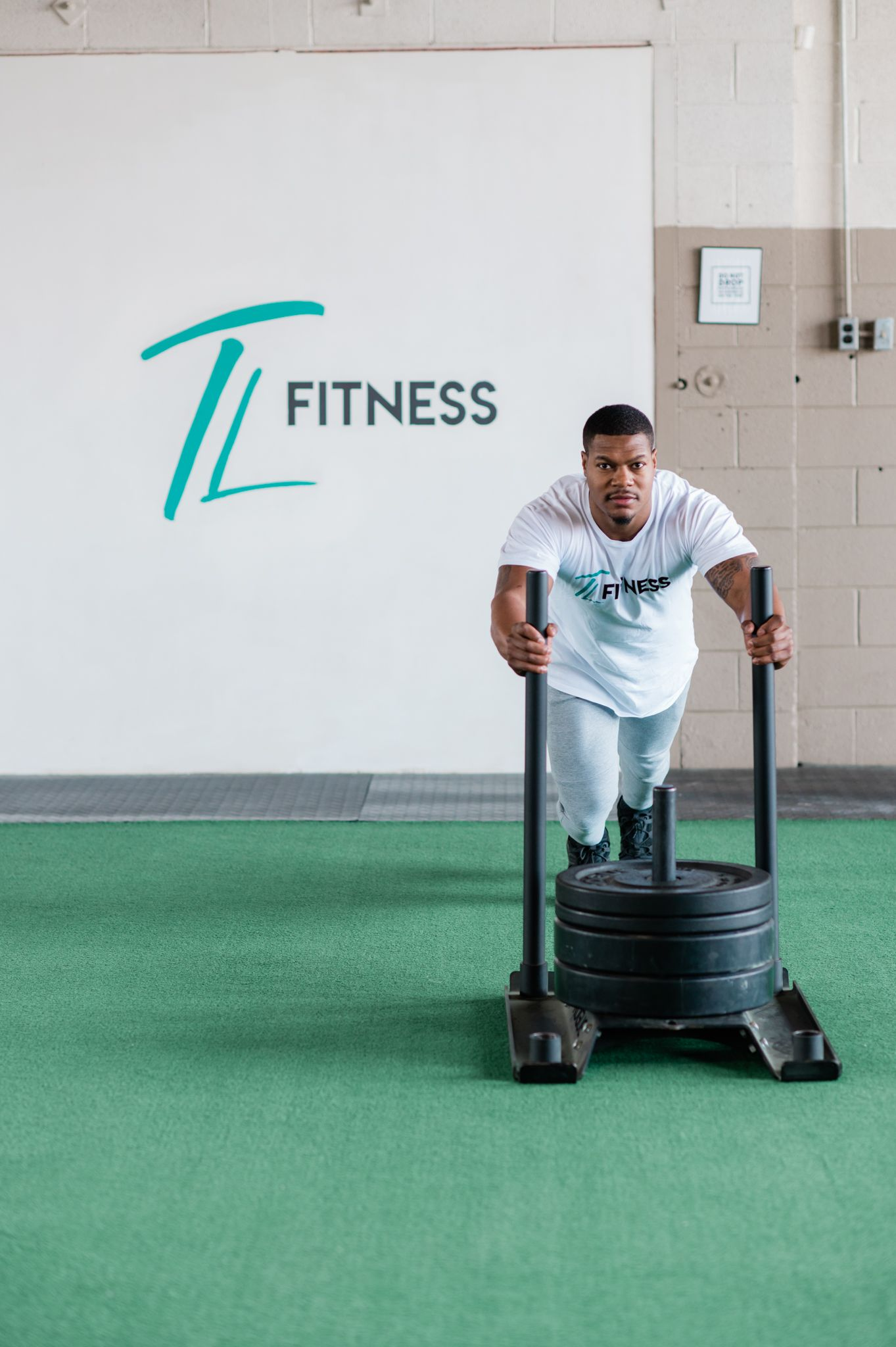 """Man looks at camera while pushing weights on a lift forward. In the background there is a wall that reads """"TL Fitness."""""""