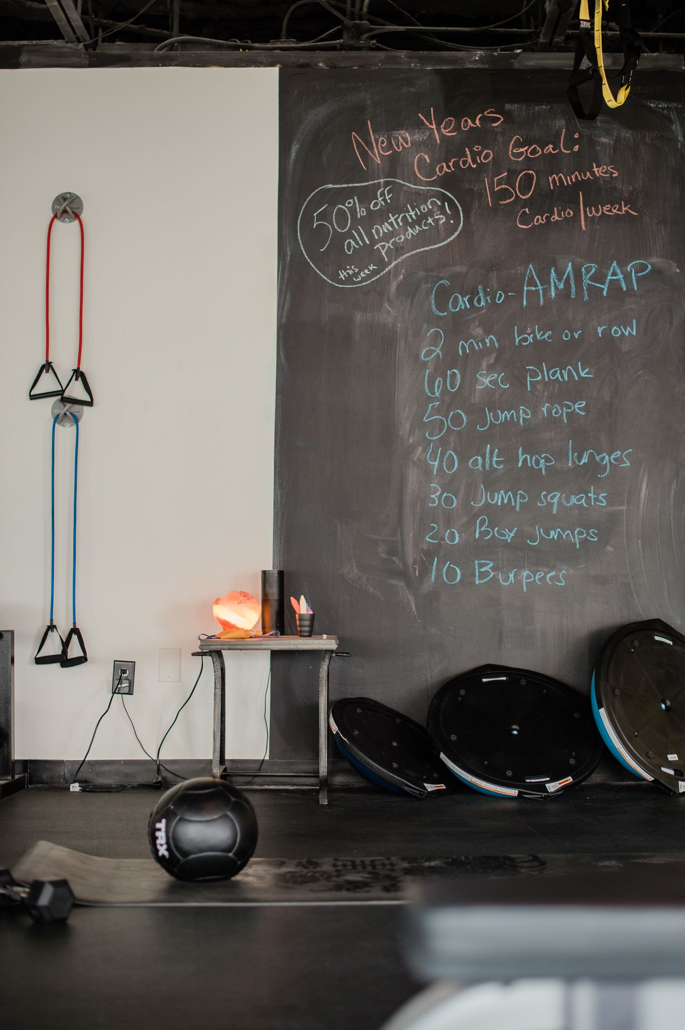 A gym with a chalkboard with exercise rep instructions written on it. Around the chalkboard are several barbell weights, a medicine ball, and other exercise equipment.
